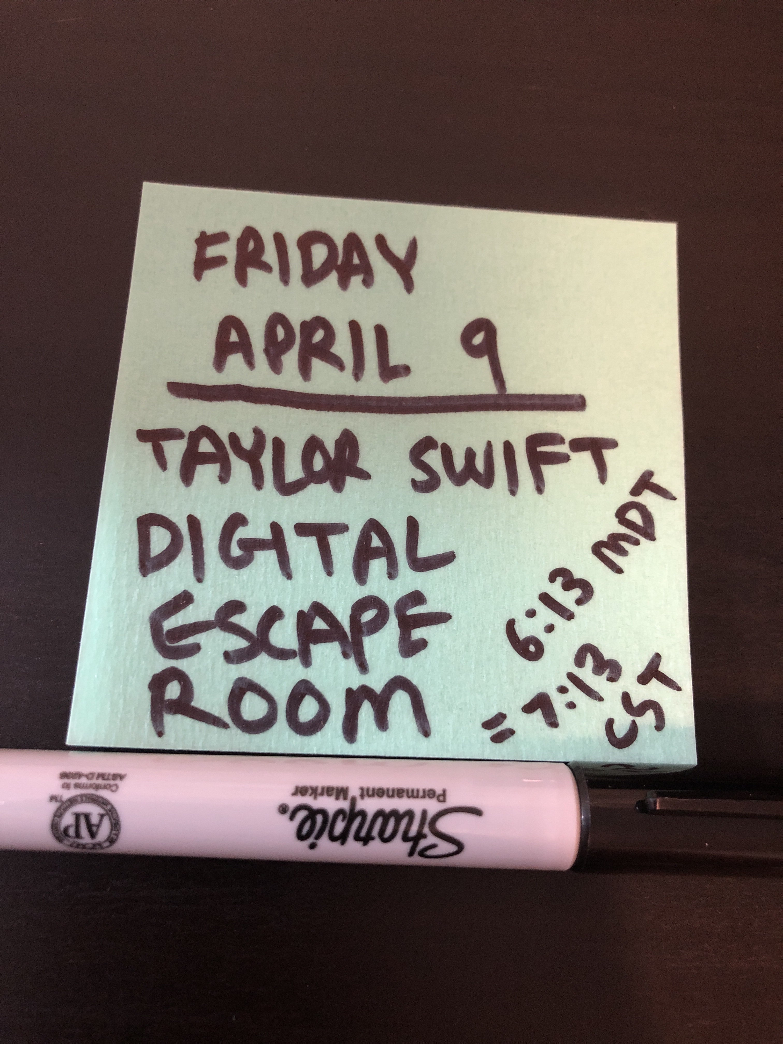 "A Sharpie next to a Post-It note which reads, ""Friday April 9. Taylor Swift Digital Escape Room. 6:13 MDT = 7:13 CST."""