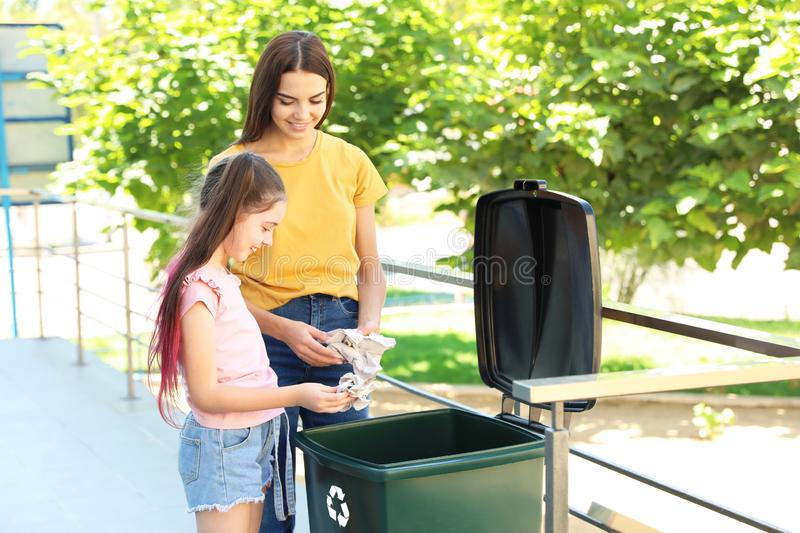 mother-her-daughter-throwing-paper-recycling-bin-mother-her-daughter-throwing-paper-recycling-bin-ou.jpg