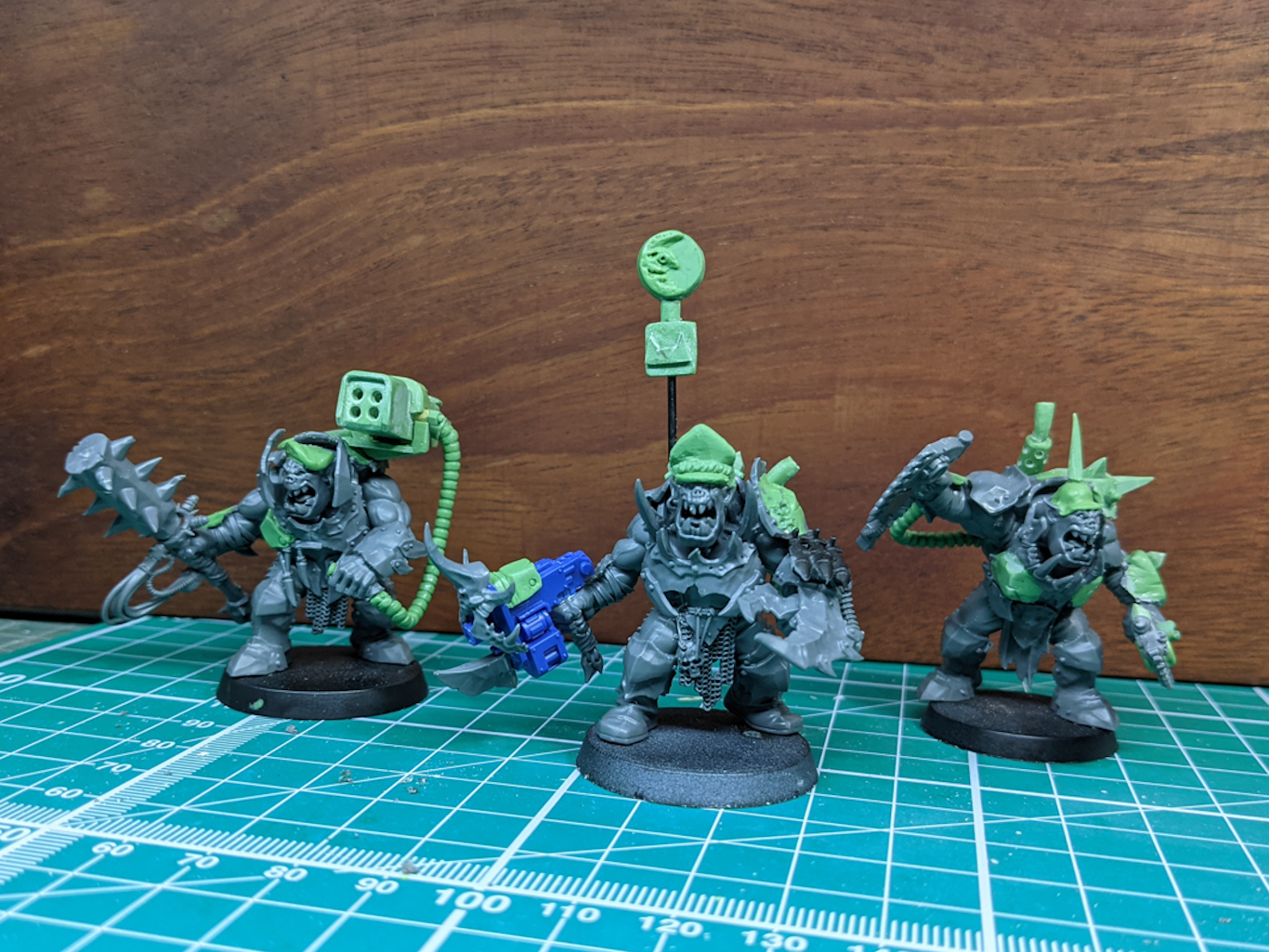 Three Ork warriors that have been extensively customised with green modelling putty, adding hats, missile launchers, and armour plating.