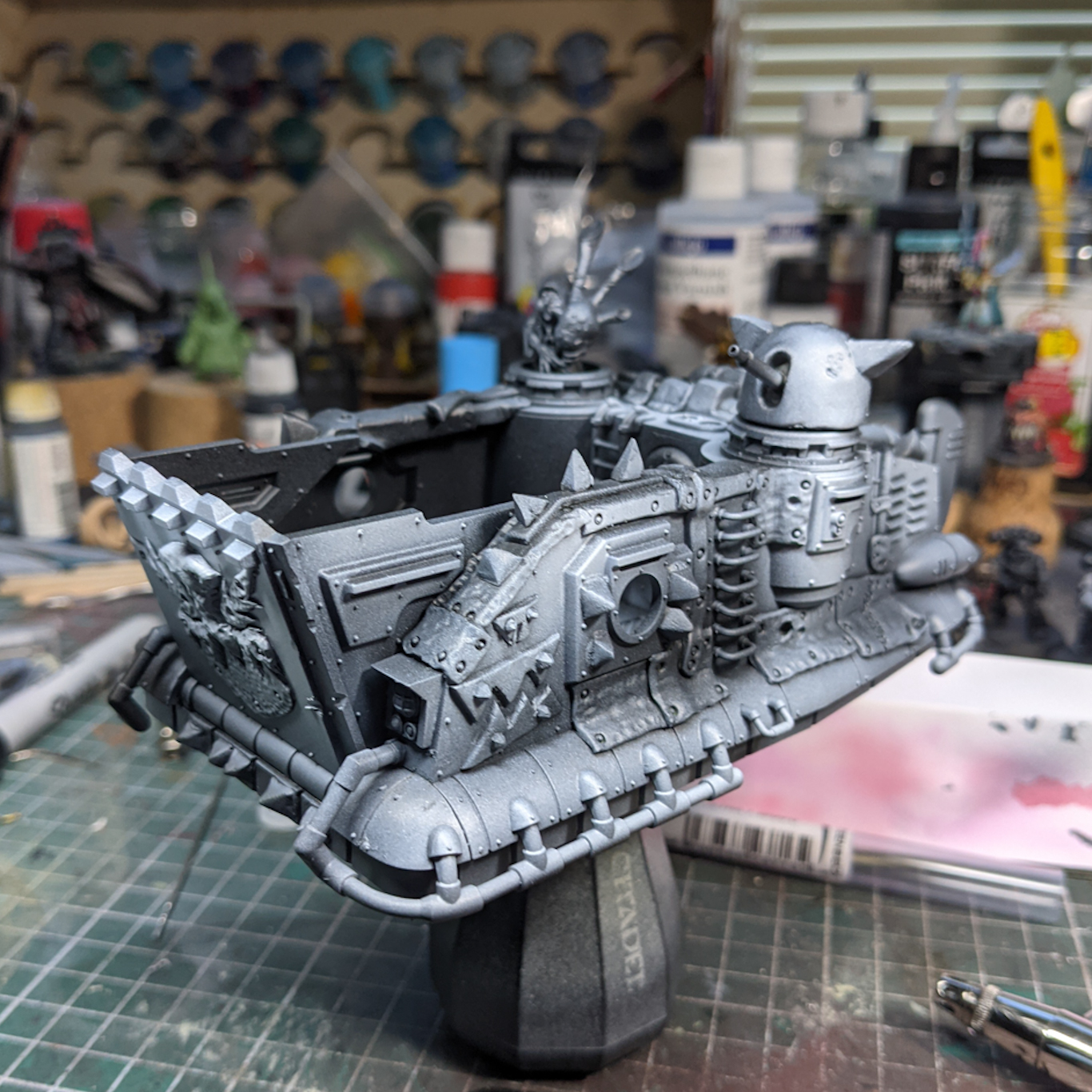 A model hovercraft covered in Orkish glyphs, spikes, and pipes.