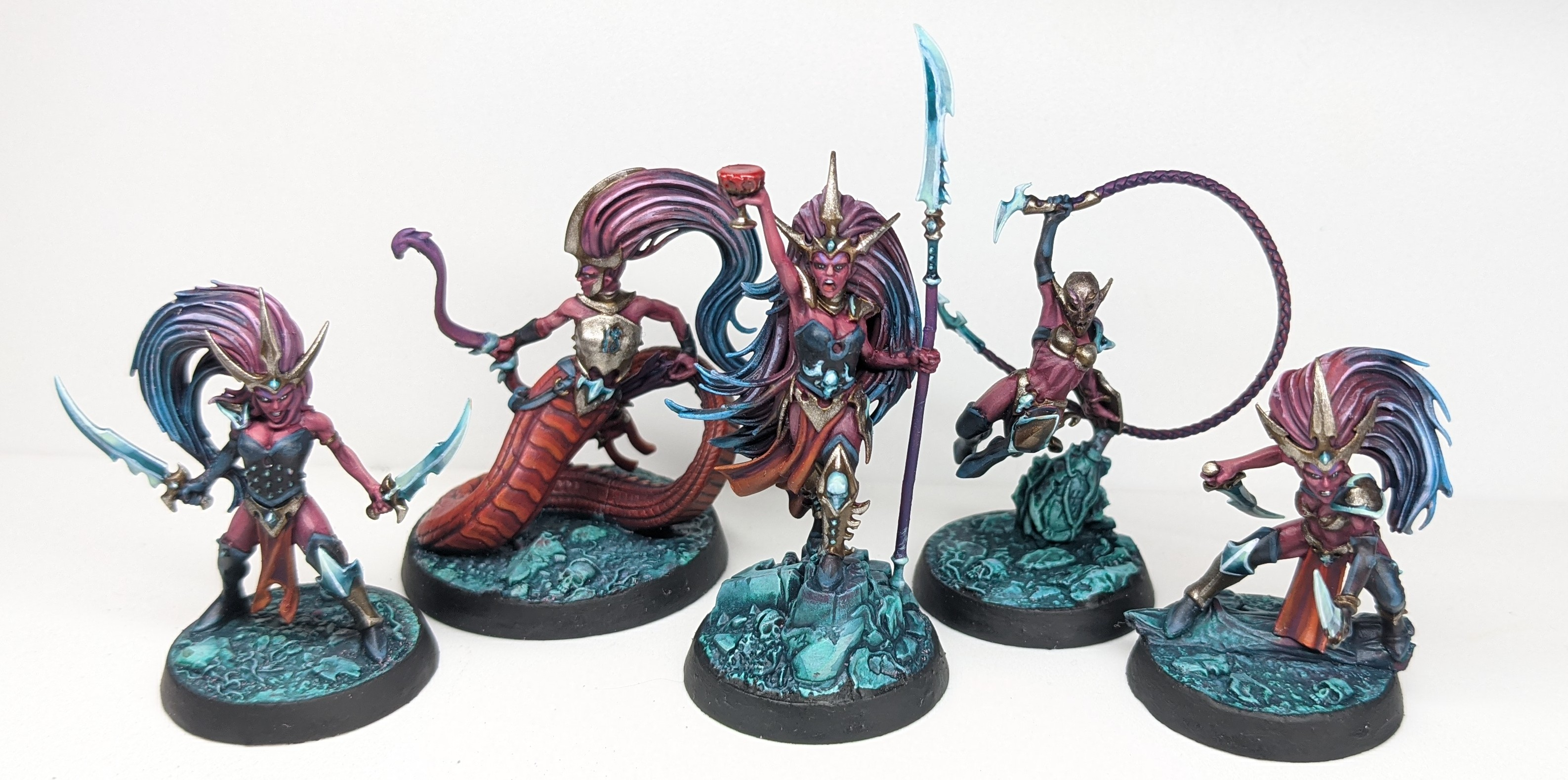 Several Model Elves with red skin and pink and blue hair.