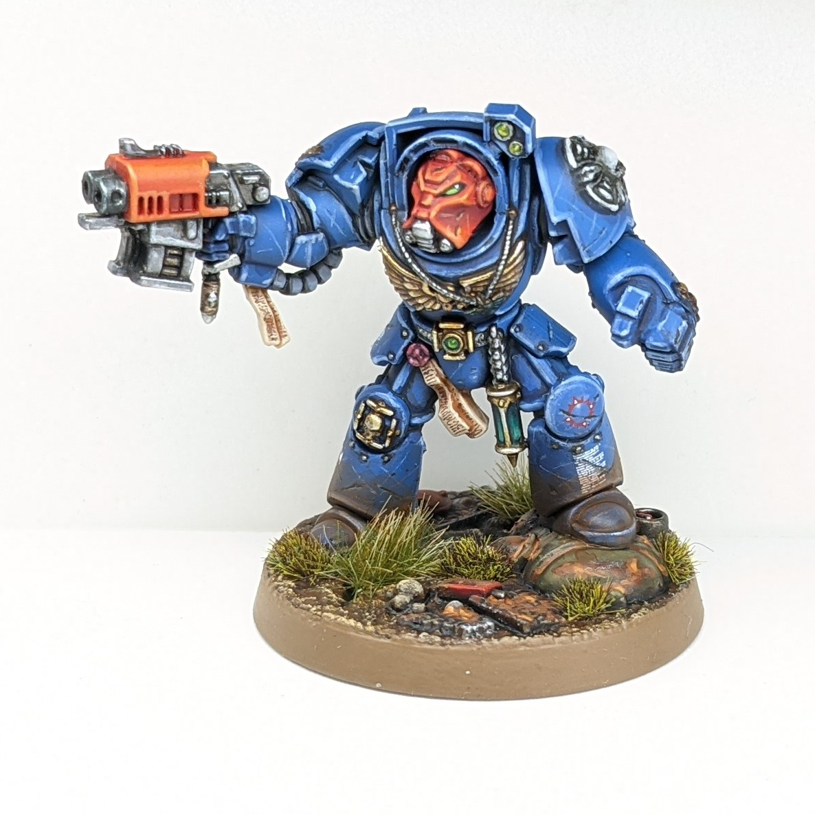 Model Ultramarine Terminator, a massively armoured warrior painted in blue, with a red helmet and weapon.