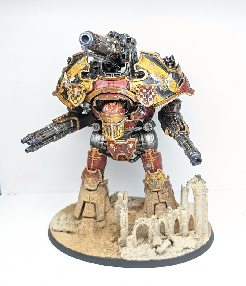 A model titan, a massive bipedal war machine with a single huge gun protruding from its back. It has red, black, and yellow armour, and its lower legs and feet are caked in sandy dirt.