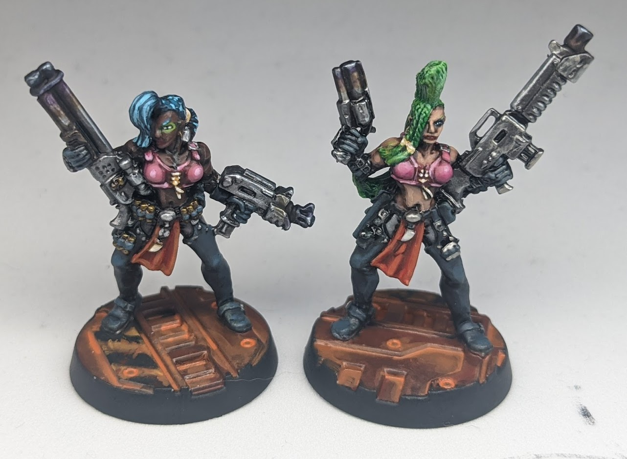 Two model women in form-fitting armour. Each has a tall, brightly-coloured hairstyle, and carries a pair of huge guns.