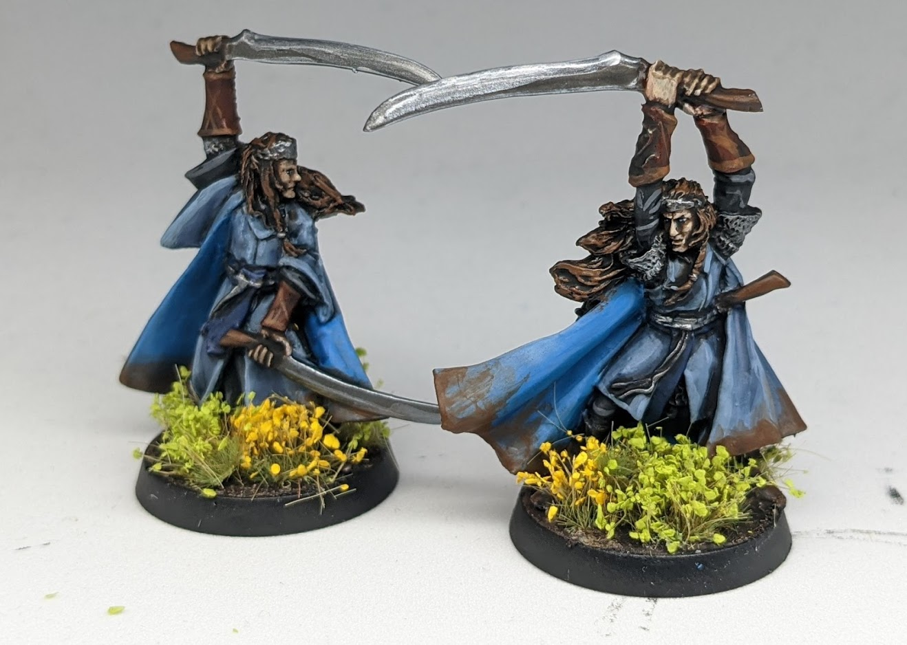Two model elves in the Lord Of The Rings style, wearing blue robes and carrying paired swords.
