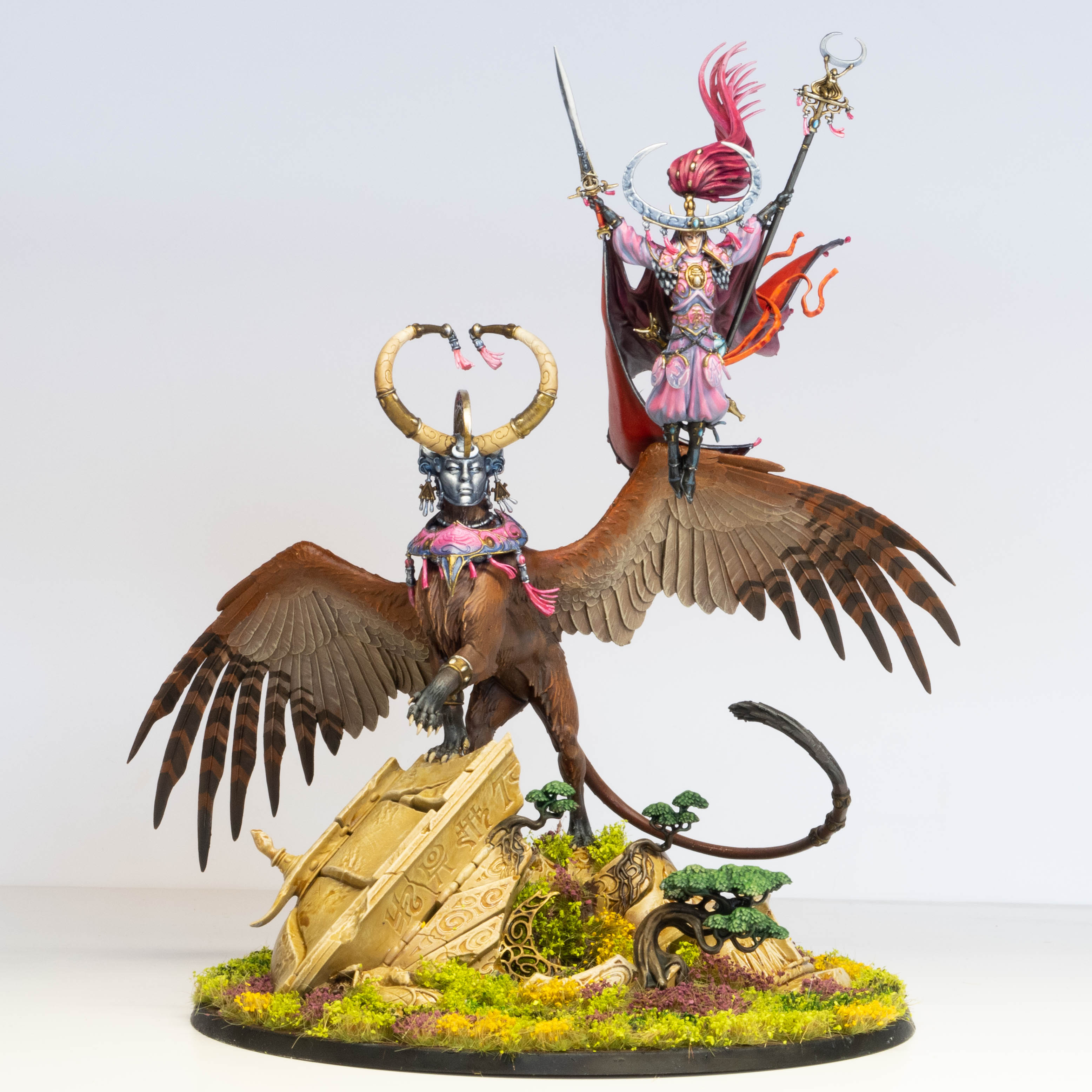 A model of Teclis, an elven wizard in ornate robes, hovering next to the Celennar, a winged feline creature with long curved horns.