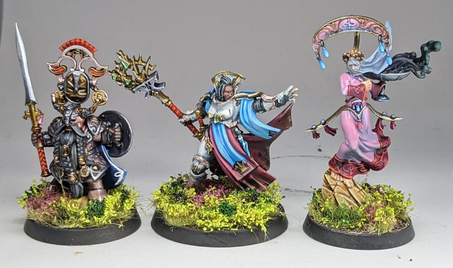 Three heroes painted in blues and pinks - a dwarf warrior, an armoured human mage, and an elf wizard with a face veil.