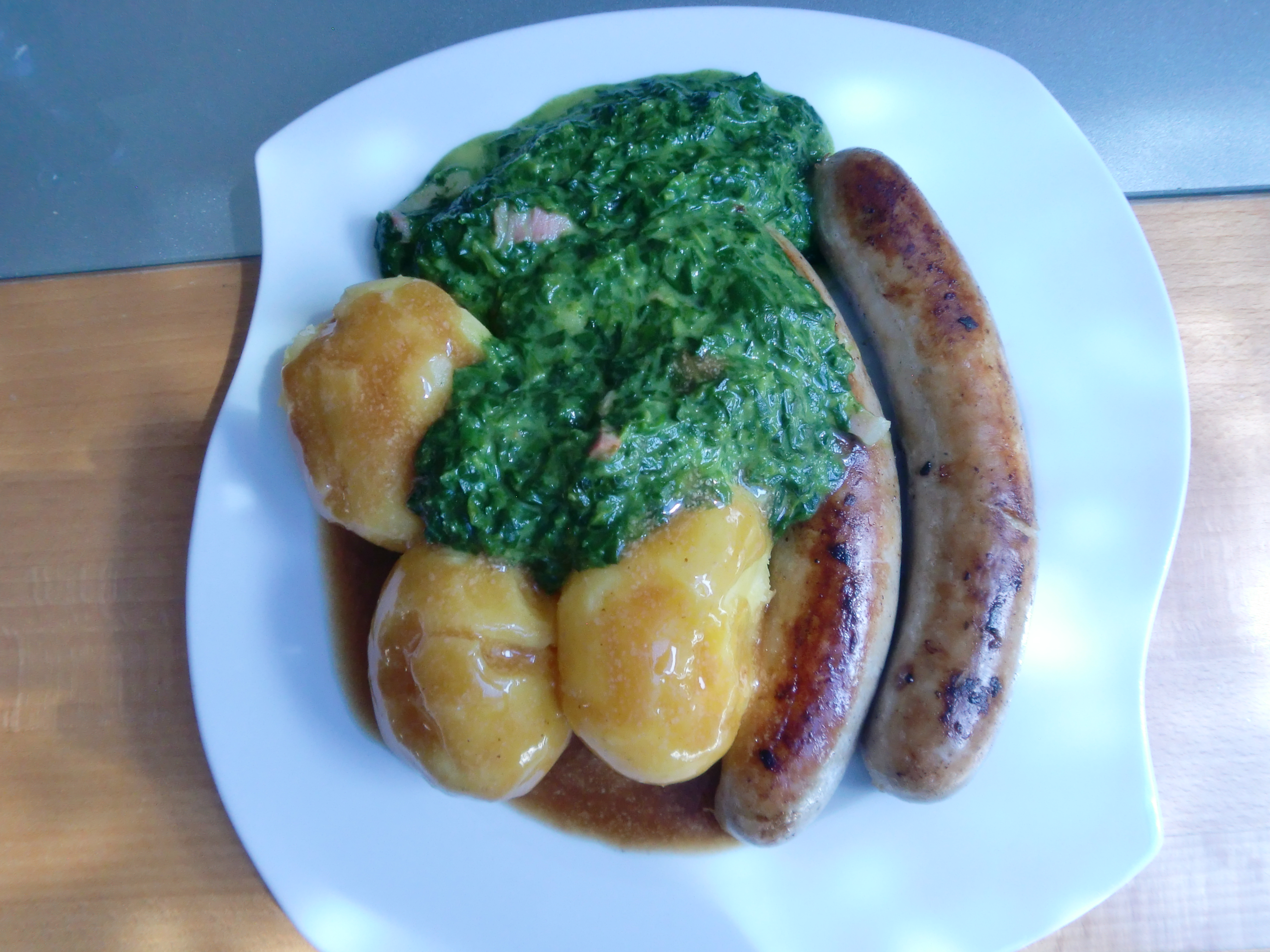 Potatoes, sausages, spinach with bacon and a sauce