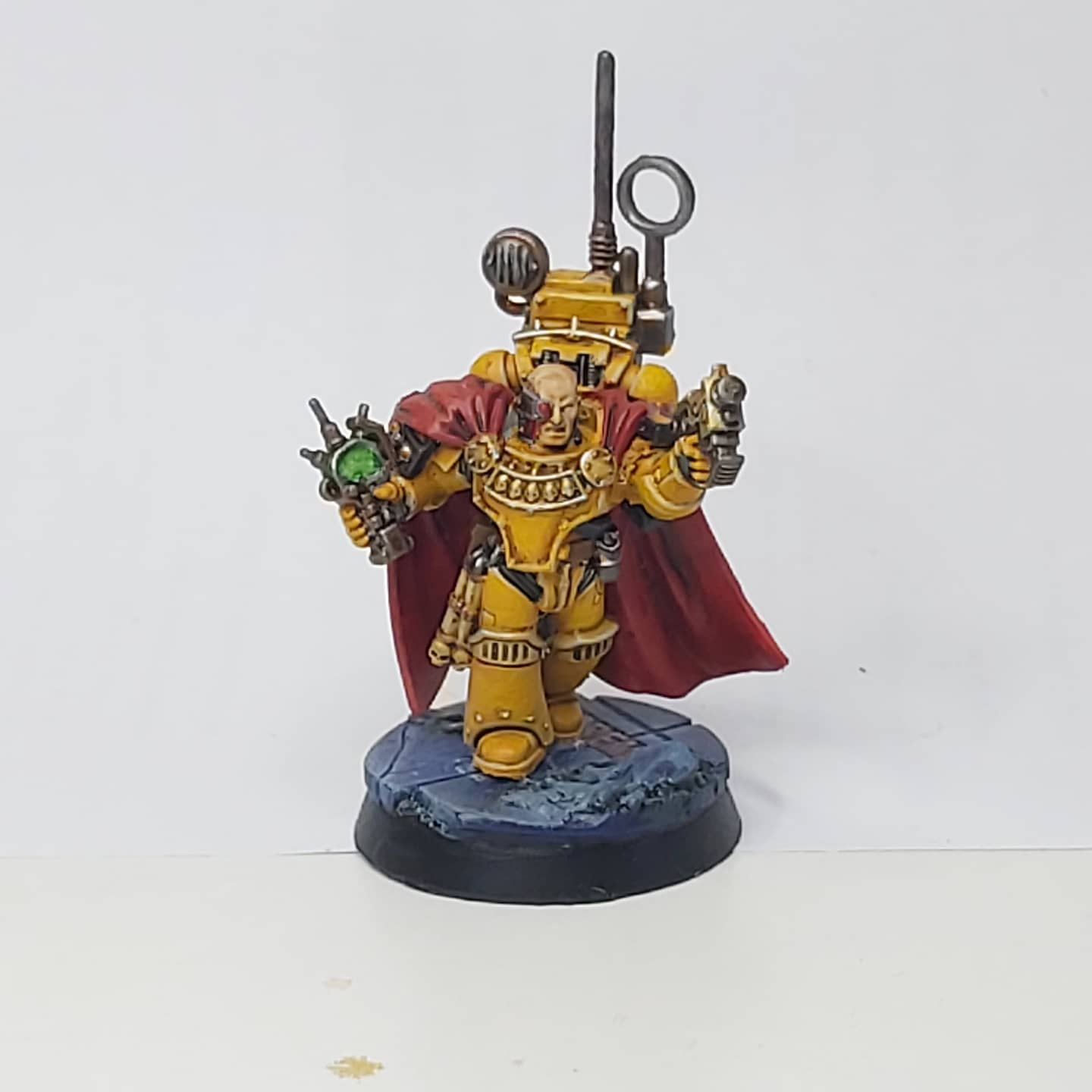A model Master Of Signal - a space marine in yellow and black armour, carrying various devices and wearing a long red robe.