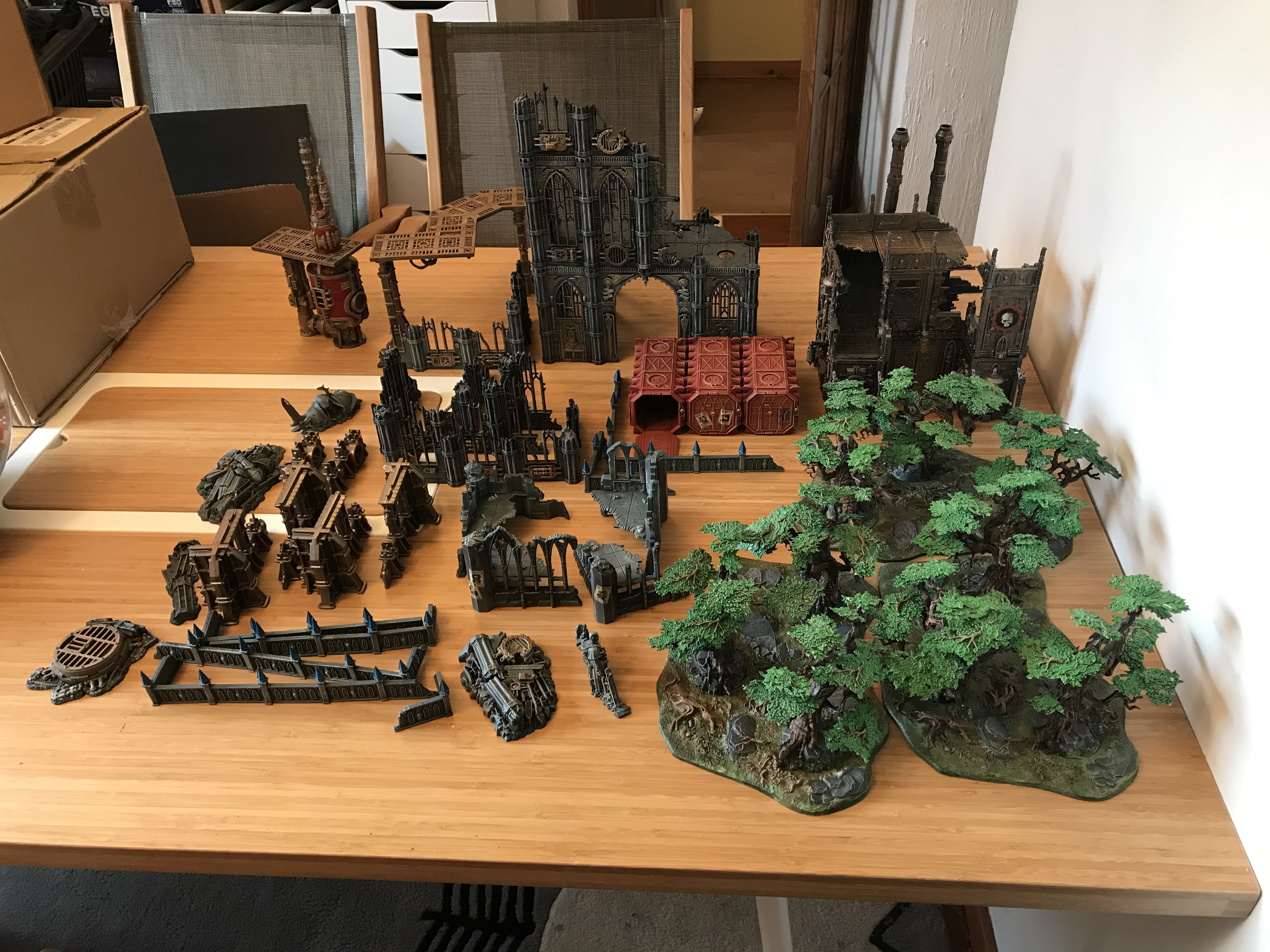 A collection of model scenery on a table, including forests, low walls, gothic ruins, and containers.