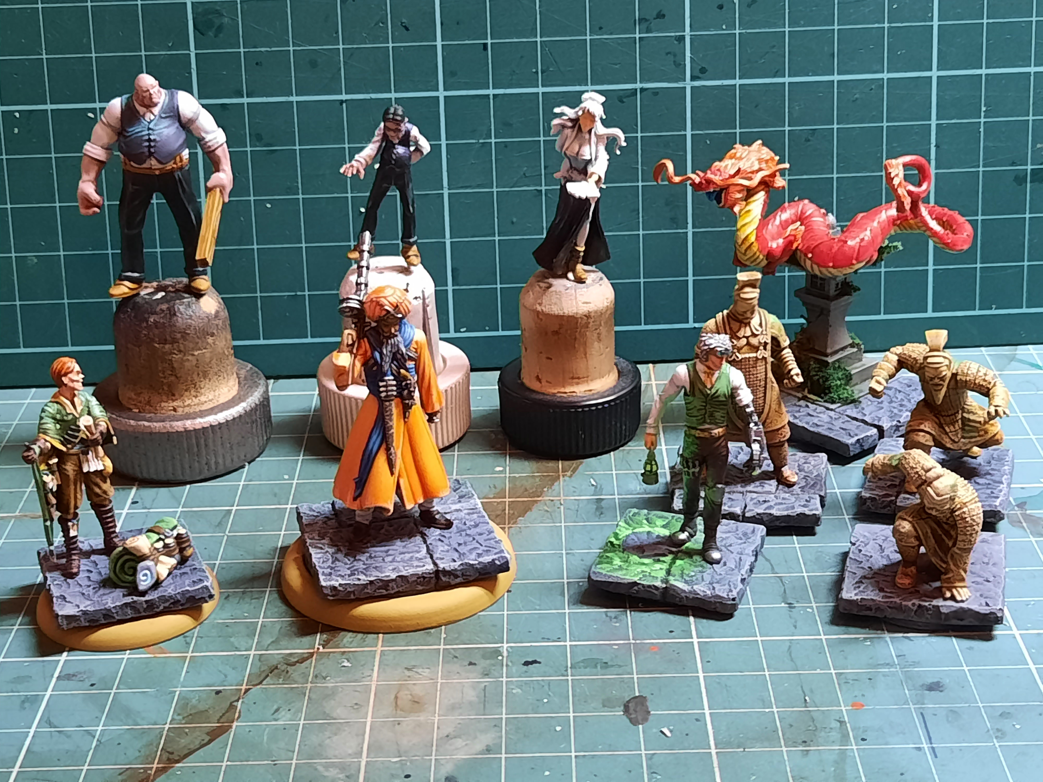 Several models mounted on temporary bases for painting, including several gothic adventurers and a dragon.