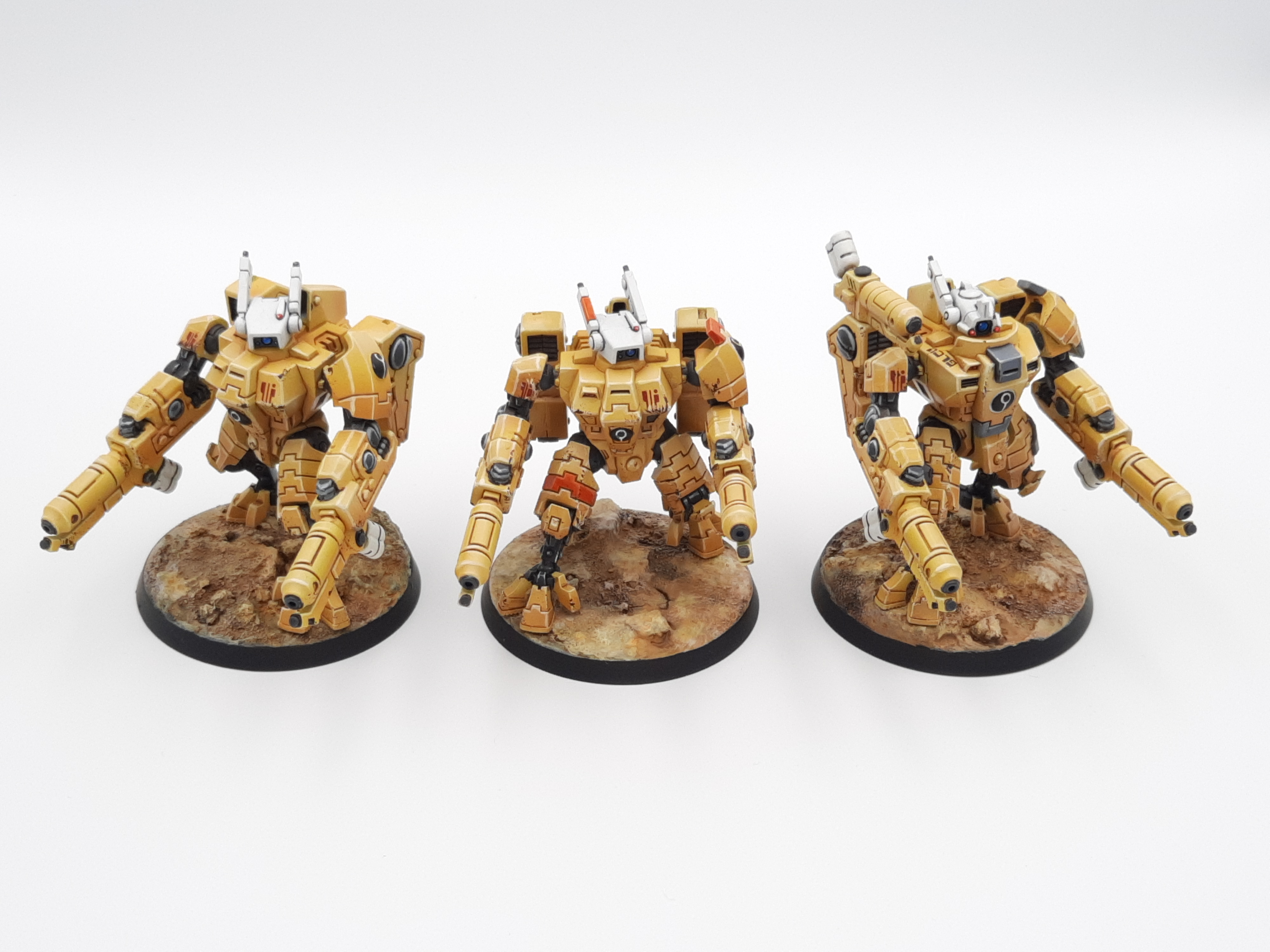 A set of three model mech suits, with crisply outlined tan armour.
