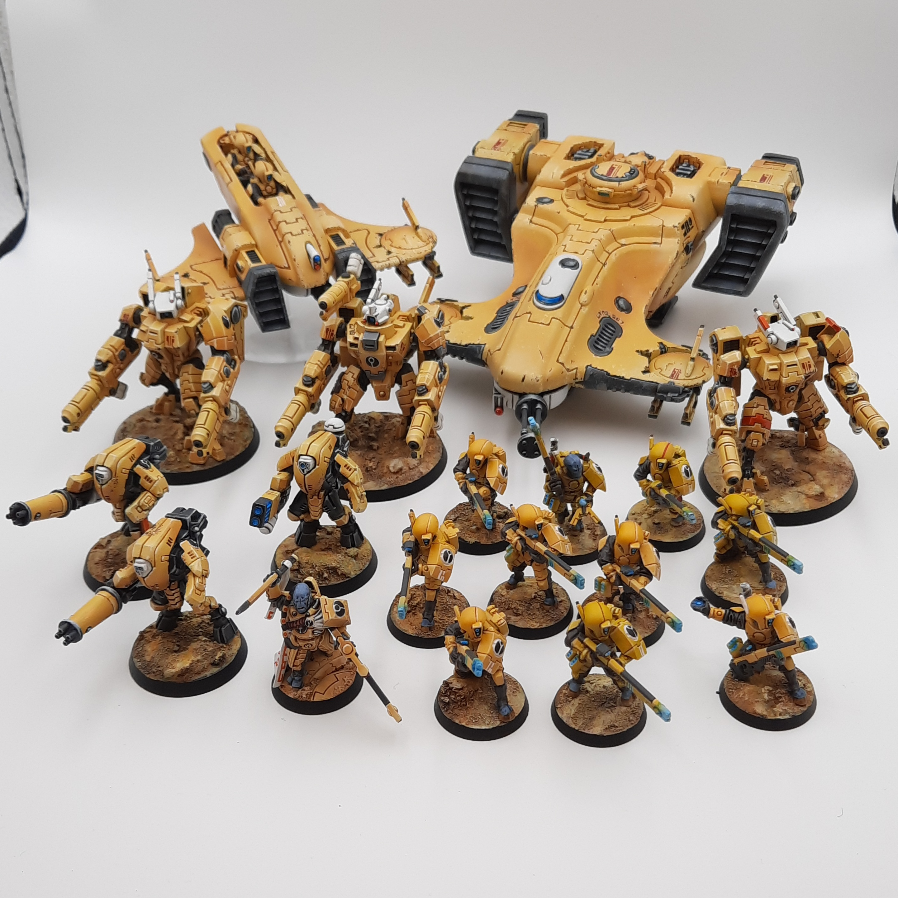 A collection of models aliens, including the battlesuits and commander above, plus line infantry and vehicles, all painted in tan and white.