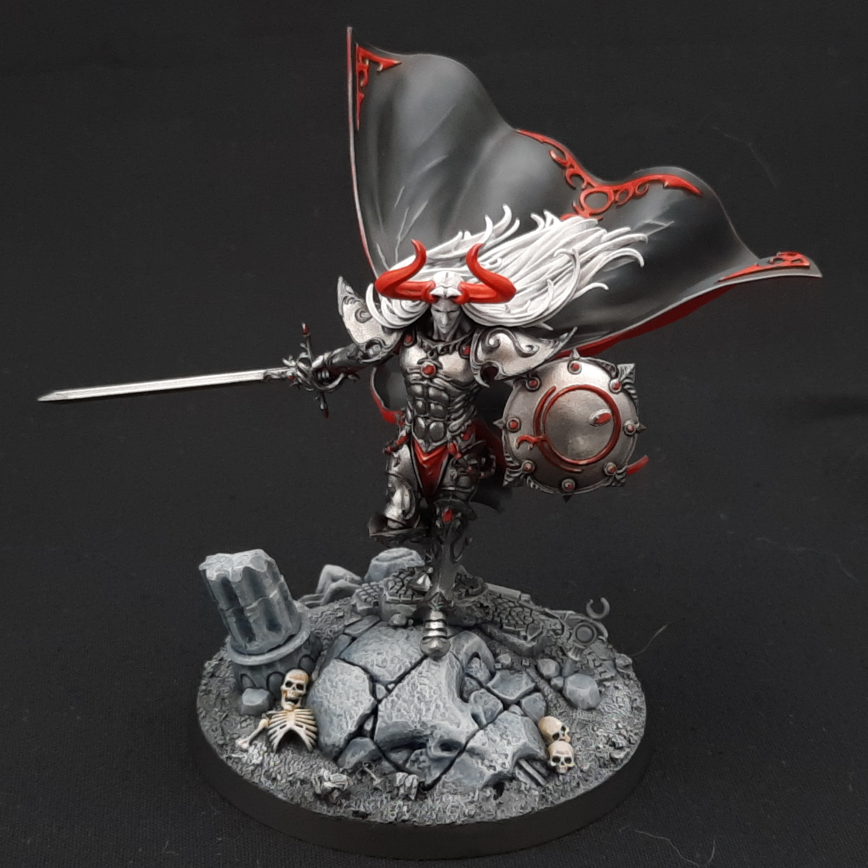 A model of Sigvald, a human in ornate armour, painted in greyscale with bright red details.