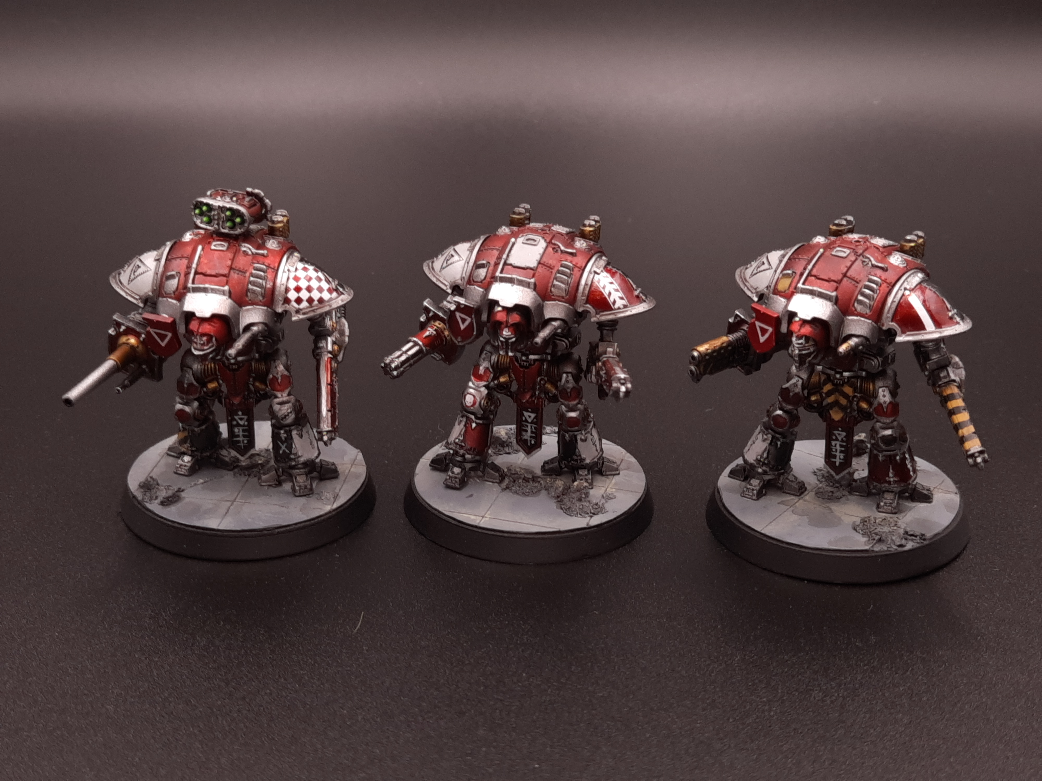 Three model mech suits in dark red and silver.