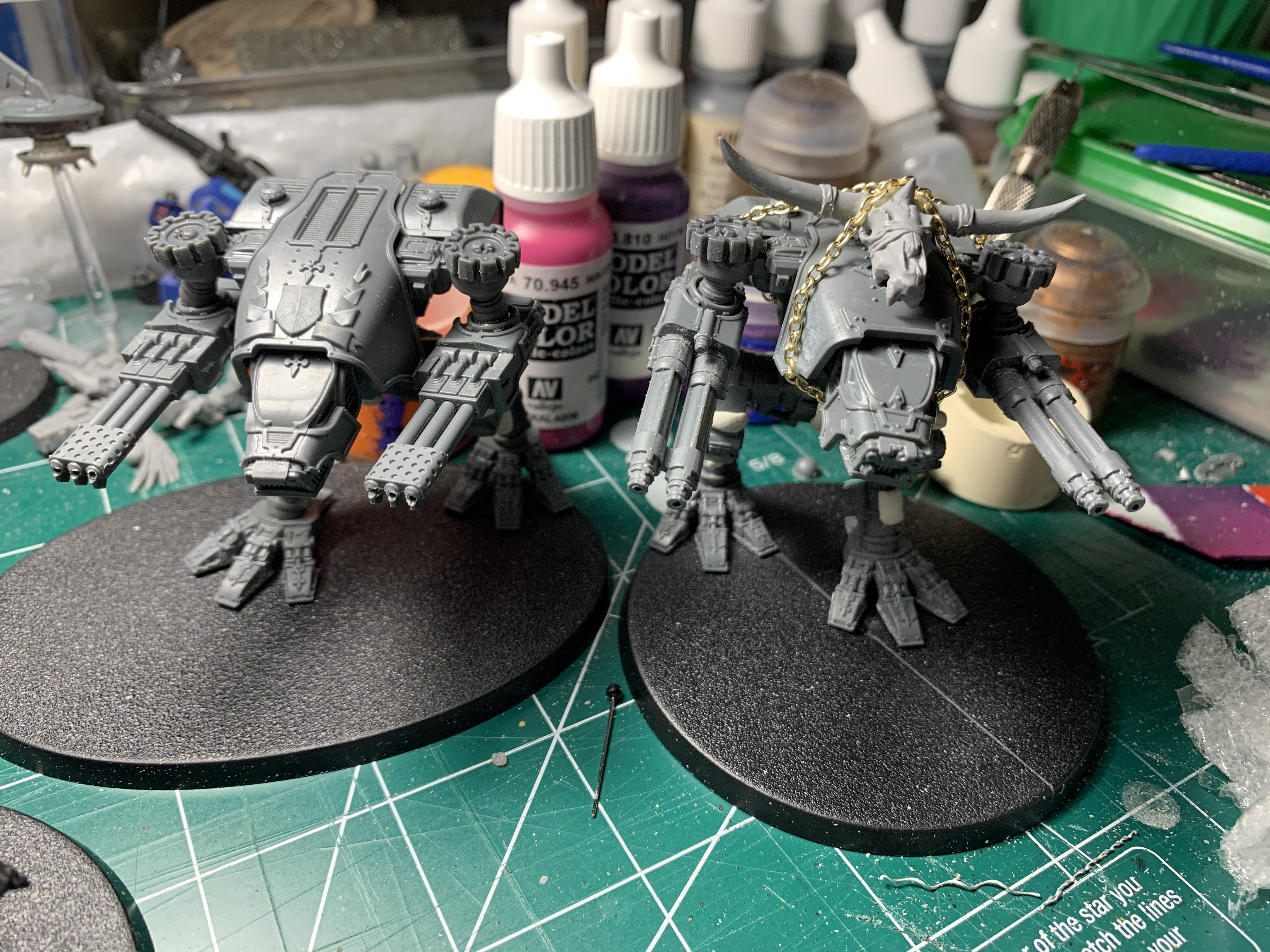Two unpainted Titan models, large bipedal vehicles. One has a huge ram's skull chained to its upper carapace.