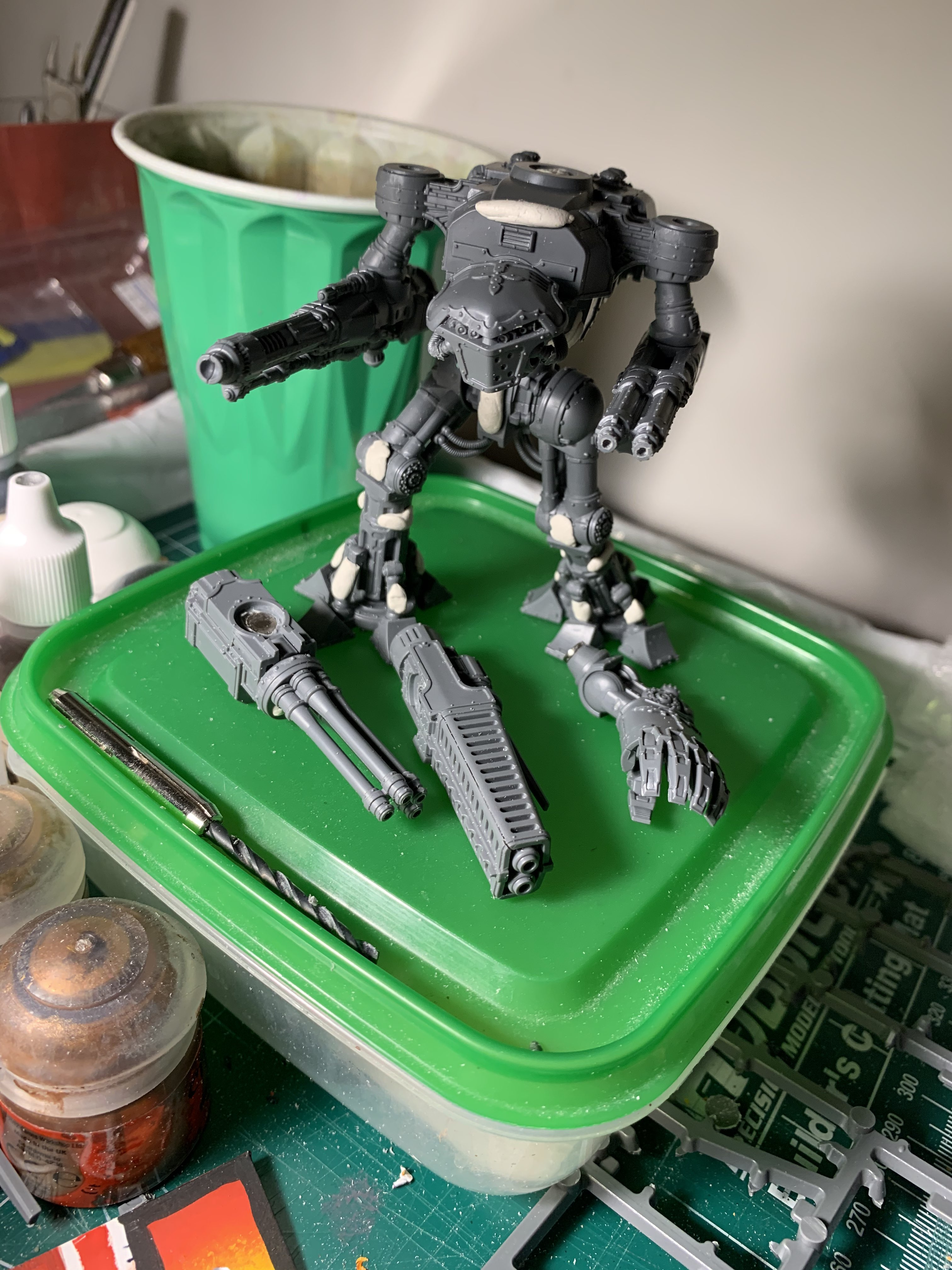 An unpainted model Reaver, a large bipedal walker, with a selection of weaponry at its feet.