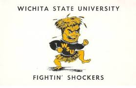 Wichita State University Fightin' Shockers Mascot. A golden shock of wheat with a face, arms and legs and an angry expression. It is wearing a black sweater emblazoned with the letters WSU